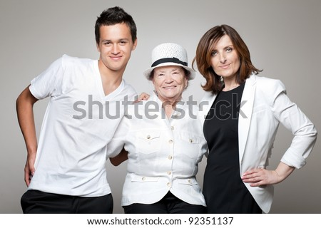 Beautiful happy three generations family posing on gray background.