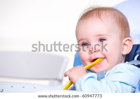 Beautiful happy toddler with spoon sitting on chair