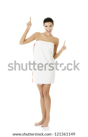 Beautiful happy woman after bath or spa, covered by white towel , pointing up