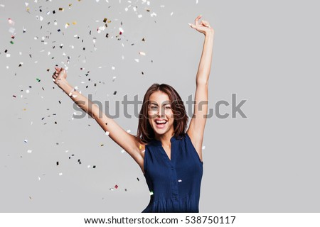 Beautiful happy woman at celebration party with confetti falling everywhere on her. Birthday or New Year eve celebrating concept #538750117
