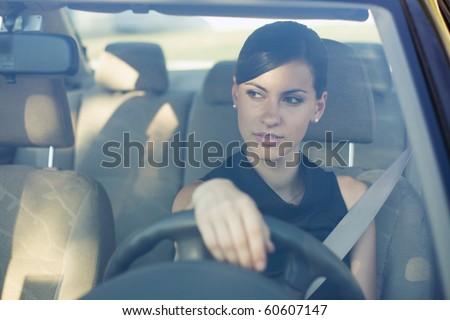 Beautiful happy woman driving her car in the evening. Windshield view