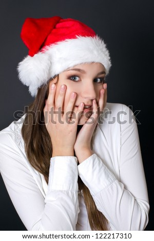 Beautiful happy woman in a Christmas hat holding her face