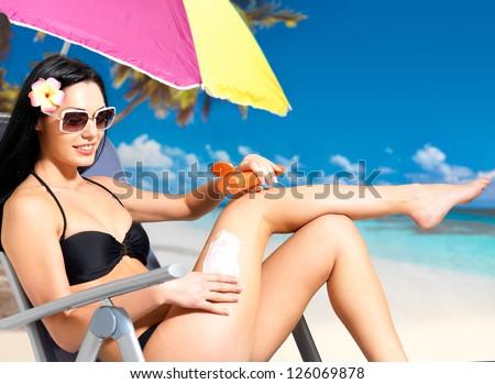 Beautiful happy woman in black bikini applying sun block cream on the tanned body.  Girl  holding orange sun tan lotion bottle.