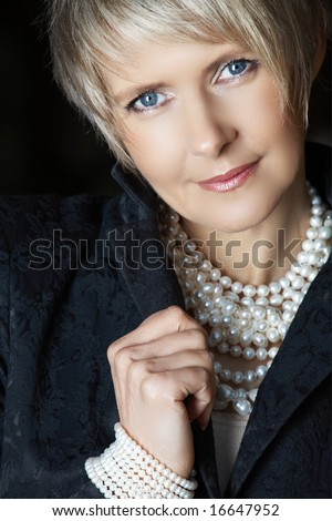 beautiful happy woman in her mid 40s with blond short hair wearing fresh water pearls