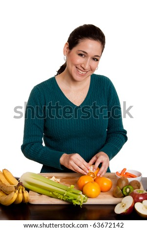 Beautiful happy woman in kitchen peeling orange preparing fruits for juice or salad, isolated.