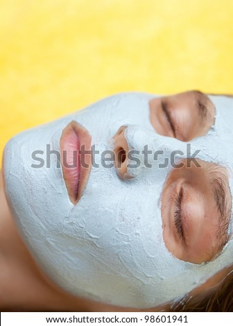 Beautiful happy woman in tropical spa making face mask treatment