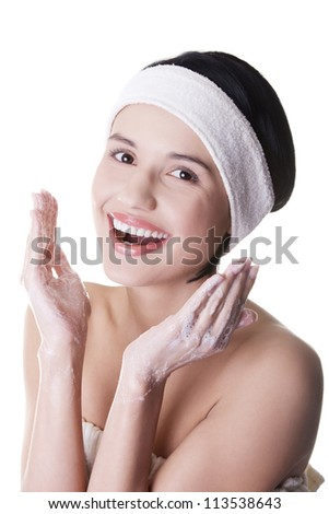 Beautiful happy woman is cleaning her face