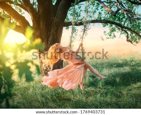 Photo of  Beautiful happy woman nymph sitting on swings. Magical fantasy swing. princess long peach color orange silk vintage dress fluttering wind. blond hair fly in motion. Tree sunshine green grass forest