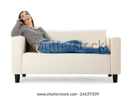 Beautiful happy woman on a white sofa making a phone call