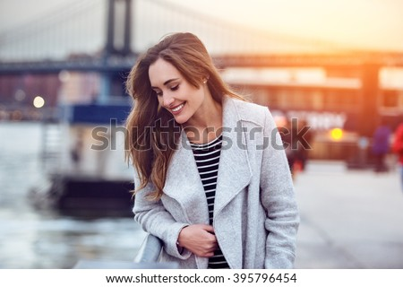 Beautiful happy woman walking near East River in New York City and looking down #395796454
