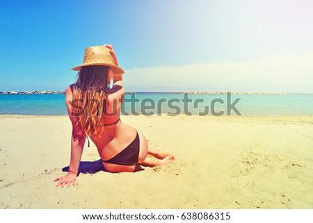 Beautiful happy woman wearing a hat and bikini resting on the beach