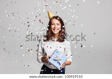 Beautiful happy woman with gift box at celebration party with confetti falling everywhere on her. Birthday or New Year eve celebrating concept #530929510