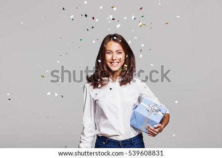 Beautiful happy woman with gift box at celebration party with confetti falling everywhere on her. Birthday or New Year eve celebrating concept #539608831