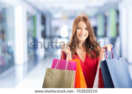 Beautiful happy woman with shopping bags in shopping mall.