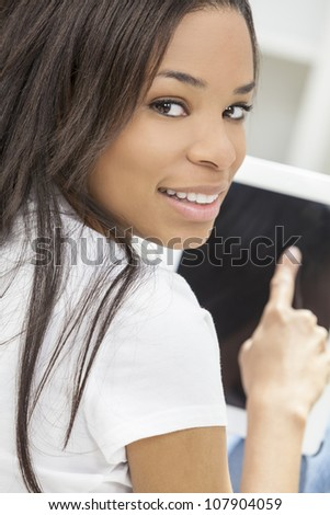 Beautiful happy young African American woman or girl smiling and using a tablet computer at home on her sofa