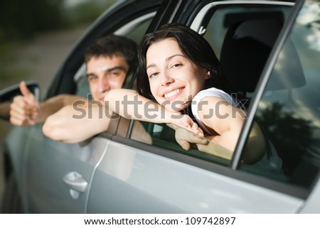 Beautiful happy young couple driving the car
