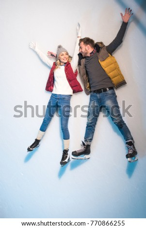beautiful happy young couple lying together on ice of skating rink #770866255
