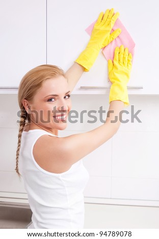 beautiful happy young housewife cleaning the furniture in the kitchen at home