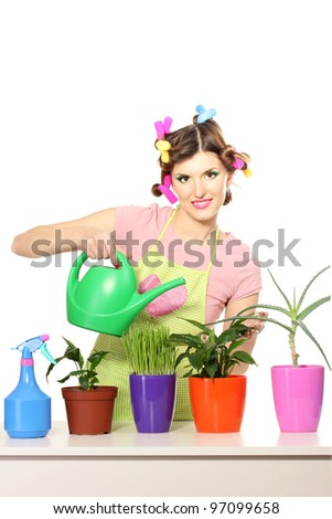 beautiful happy young housewife watering plants in flowerpots isolated on white - stock photo