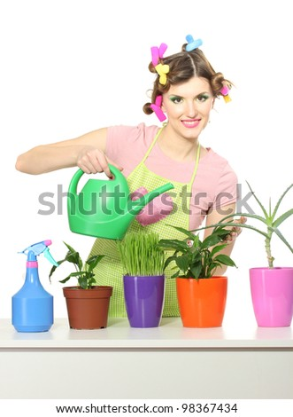 beautiful happy young housewife watering plants in flowerpots isolated on white