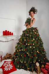 Beautiful happy young lady with a Christmas pine wreath on her head and fashione xmas tree dress, decorated with Christmas balls, berries and snowflakes. New Year Concept