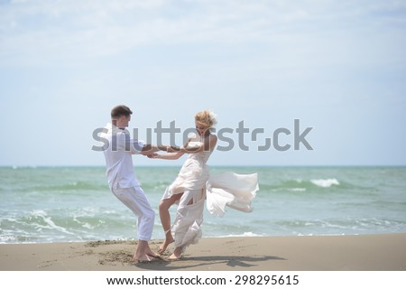 Beautiful happy young wedding couple of man and woman in white spinning on ocean beach coast on windy weather sunny day outdoor on blue sky background, horizontal picture