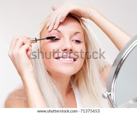 beautiful happy young woman doing makeup and applying mascara