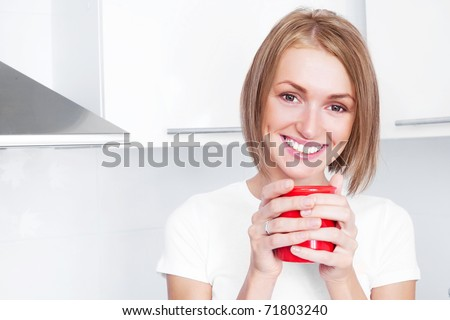 beautiful happy young woman drinking coffee at home in the morning