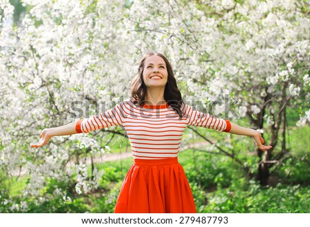 Stock Photo Beautiful happy young woman enjoying smell in a flowering spring garden