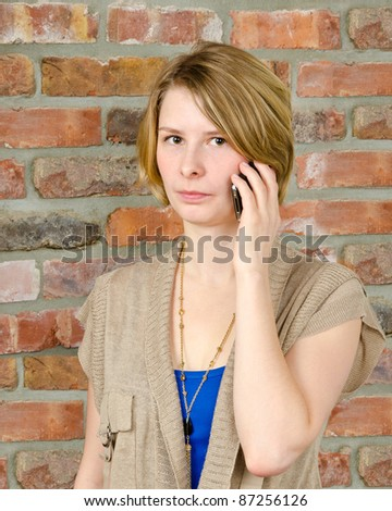 Beautiful happy young woman standing against brick wall and using cellphone
