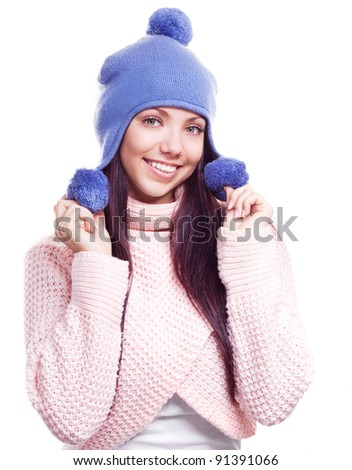 beautiful happy young woman wearing a high neck sweater and a hat with pom-poms, isolated against white background