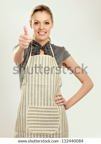 Beautiful happy young woman wearing kitchen apron and gesturing thumbs up, isolated on white - stock photo