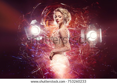beautiful happy young woman with stunning figure and bright makeup wearing evening dress surrounded by light. studio lights. holiday mood. copy space. #753260233