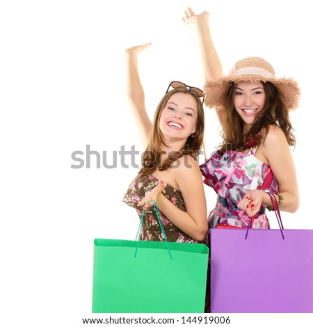 Beautiful happy young women with colored shopping sale bags in summer clothes pointing with hands up into the copyspace over white