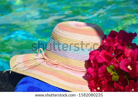 Beautiful hat and flowers at the pool. Sea vacation background. Vacation in the tropics. Holidays in topical countries.
