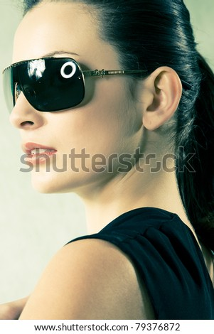 beautiful head shot of brunette with sunglasses photographed in studio.