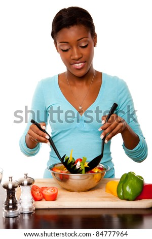 Beautiful health conscious young woman tossing healthy organic salad in kitchen, isolated.