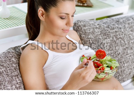 Beautiful healthy pregnant woman  eating vegetable salad