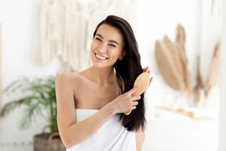 Beautiful healthy silky hair after beauty treatment during covid-19 pandemic. Smiling millennial pretty brunette lady in towel with combing long shiny hair with comb in morning, on bathroom background