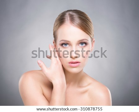 Beautiful healthy woman touching her cheek with a hand.