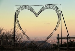 Beautiful heart shaped wire frame with pink lights at sunset