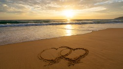 Beautiful hearts symbol on beach sand over sunset Valentines day on the beach Gift celebration romantic light sunset A heart is drawn on the seashore The inscription on the beach sand.