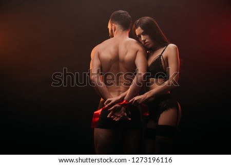 beautiful heterosexual couple with red ribbon in smoky room #1273196116