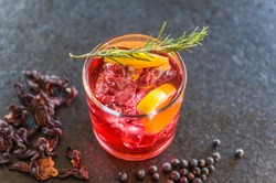 Beautiful hibiscus kombucha cocktail with gin and vodka, decorated with rosemary branch.