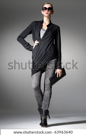 Beautiful high fashion model in modern clothes hold purse posing