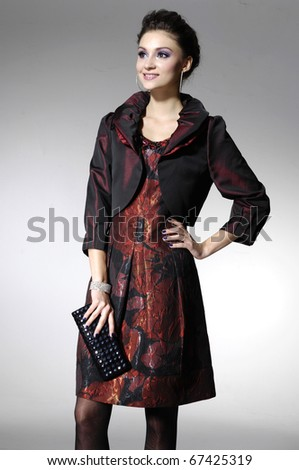 Beautiful high fashion model in modern clothes hold purse posing in light background