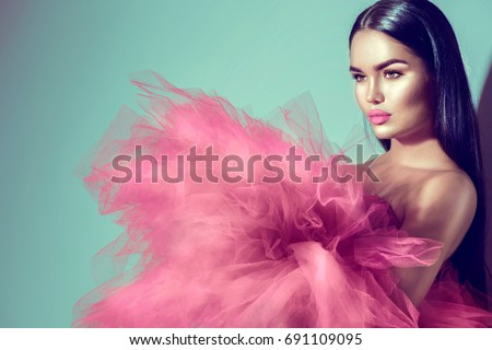Beautiful High fashion woman in violet color dress posing in studio. Gorgeous brunette model girl with beautiful hairstyle and make-up, Wearing Stunning evening red dress with long gown of tulle  - Shutterstock ID 691109095