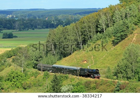 Beautiful hilly landscape with an old retro steam train