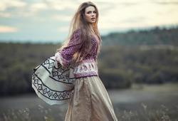 Beautiful hippie girl jumping outdoors at sunset. Boho fashion style