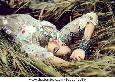 Beautiful hippie girl lying in a grass. Modern boho style. Beauty, fashion,  #1082340896